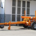Controlled single-axle trailer with trailer stakes for pole transports