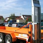 Tandem inloader trailer for small machines with hinged ramp planks